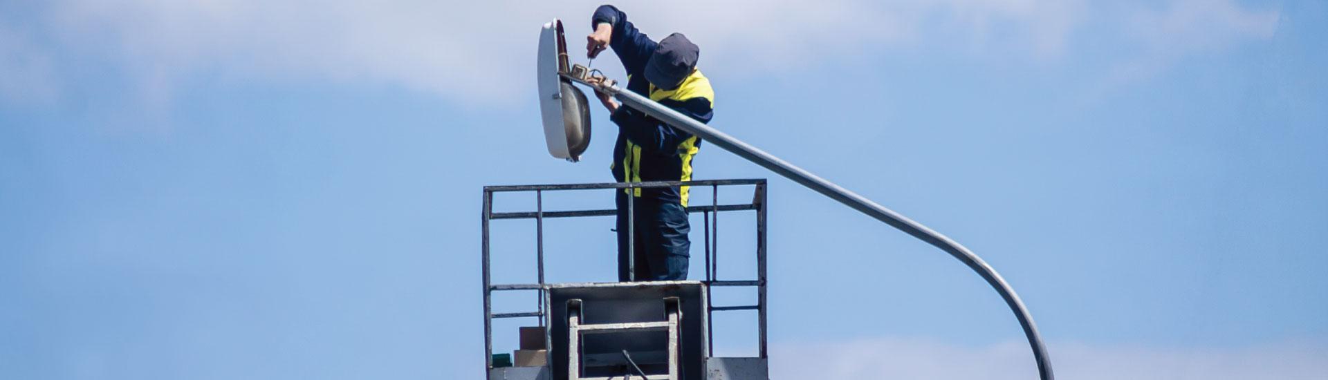 A journeyman electrician repairs a parking lot lighting fixture from a bucket truck