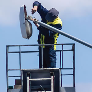A Journeyman Electrician Repairs A Parking Lot Lighting Fixture From A Bucket Truck