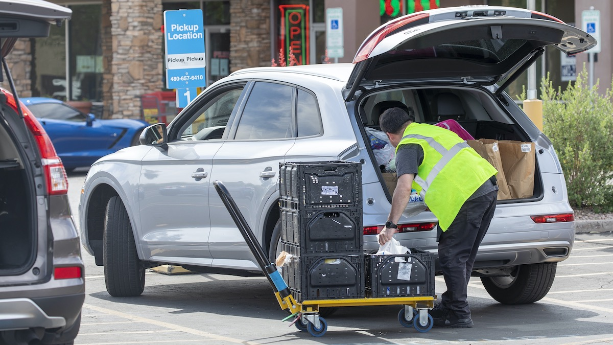 Grocery Store Employee Loads Online Order Items in Parking Lot Pickup Location